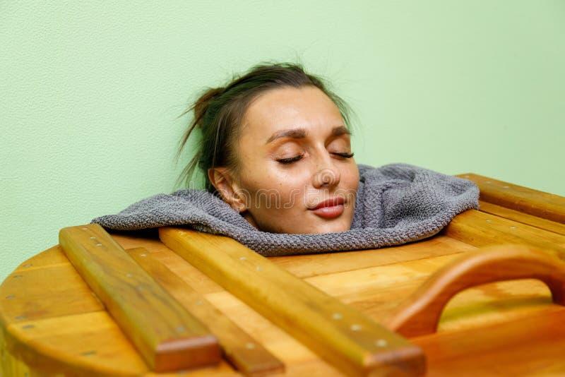 Donna che ha trattamento della stazione termale nella sauna di legno del barilotto, vasca del cedro fotografia stock