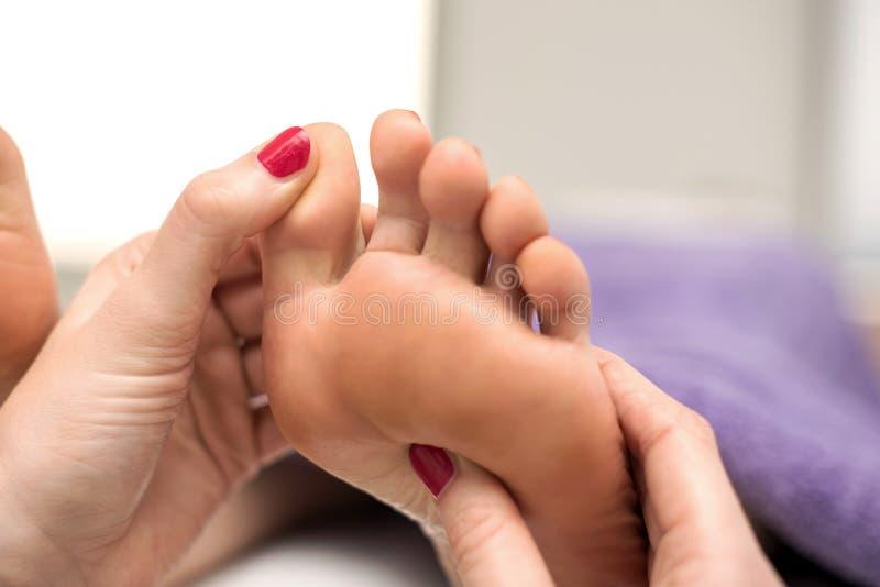Donna che ha un trattamento di pedicure ad una stazione termale o ad un salone di bellezza con immagini stock