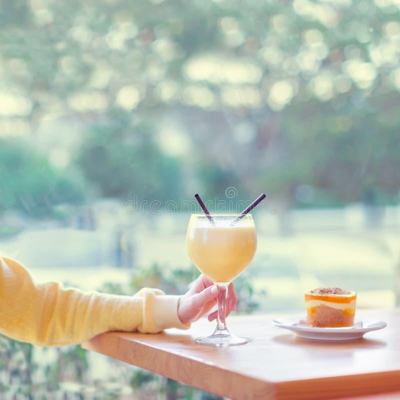 Donna che ha un vetro del frullato della banana con il dessert in caffè fotografia stock