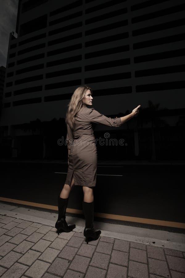 Donna che hitching un giro nello scuro immagine stock libera da diritti