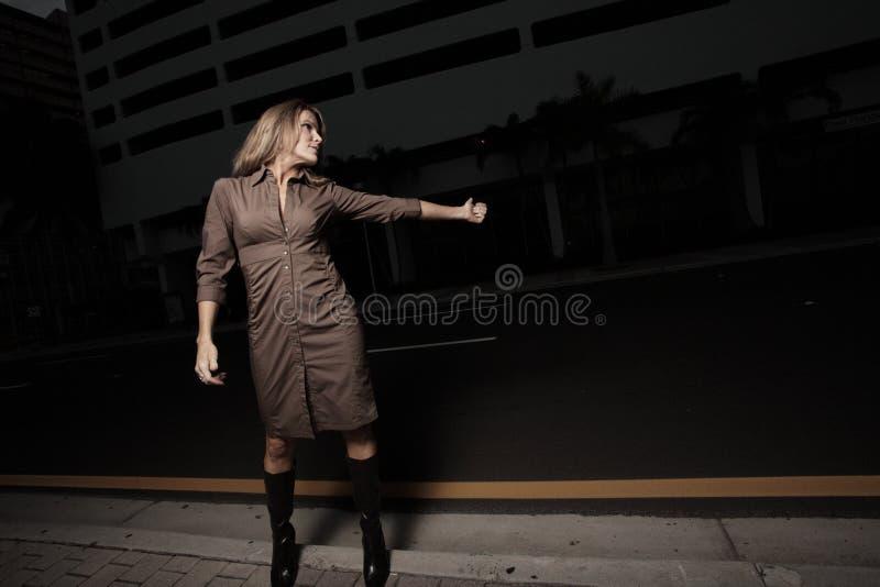 Donna che hitching un giro nello scuro fotografia stock