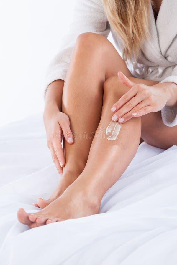 Donna che idrata le sue gambe immagini stock