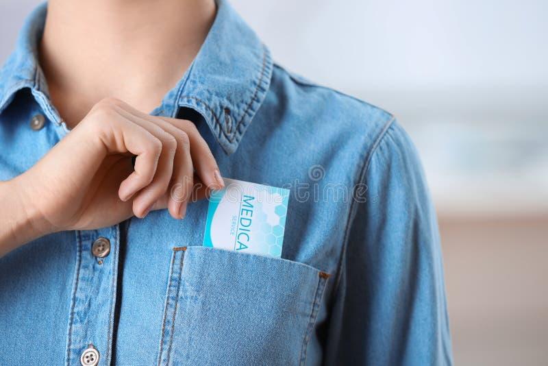 Donna che immette biglietto da visita nella tasca sul fondo vago Servizio medico fotografia stock