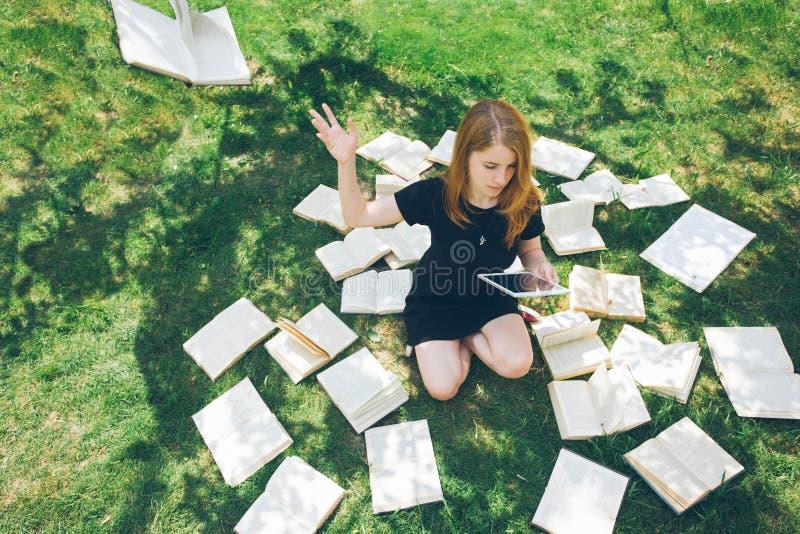 Donna che impara con il lettore ed il libro del libro elettronico Scelta fra tecnologia educativa moderna ed il metodo tradiziona immagini stock