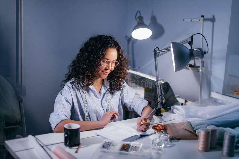 Donna che impara i segreti di cucito riassunto di scrittura di progettazione dei clothers a casa fotografia stock libera da diritti