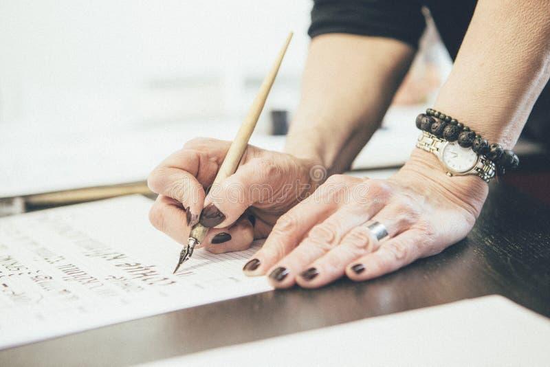 Donna che impara iscrizione con le spazzole e penna calligrafica sulla a fotografia stock libera da diritti