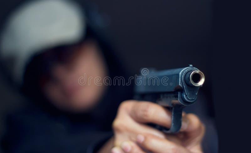 Donna che indica una pistola all'obiettivo su fondo scuro immagini stock