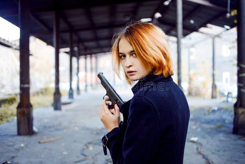 Donna che indica una pistola Fucilazione della ragazza della mafia a qualcuno sulla via immagine stock libera da diritti