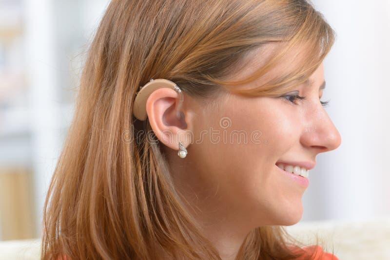 Donna che indossa aiuto sordo immagini stock