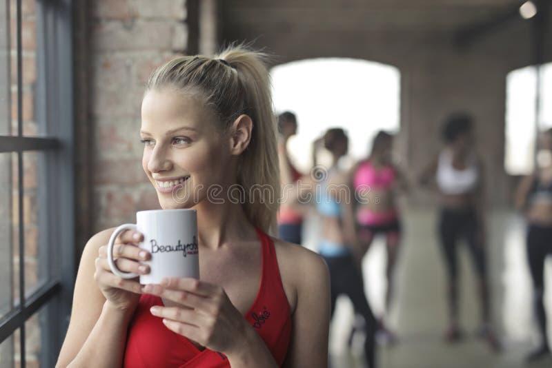 Donna che indossa canottiera sportiva rossa che tiene tazza ceramica bianca immagine stock
