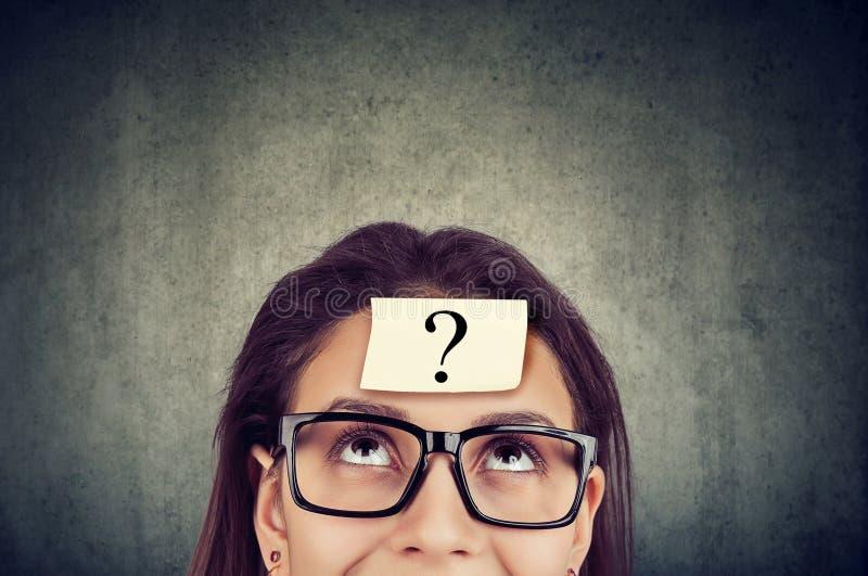 Donna che indossa i vetri neri con il punto interrogativo sul cercare della fronte immagine stock