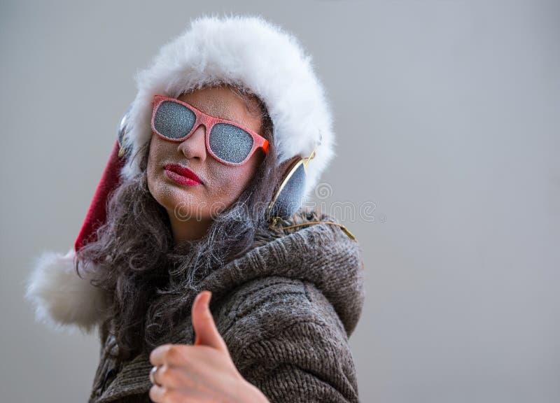 Donna che indossa il cappello e gli occhiali da sole di Santa Claus che ascoltano la musica fotografia stock