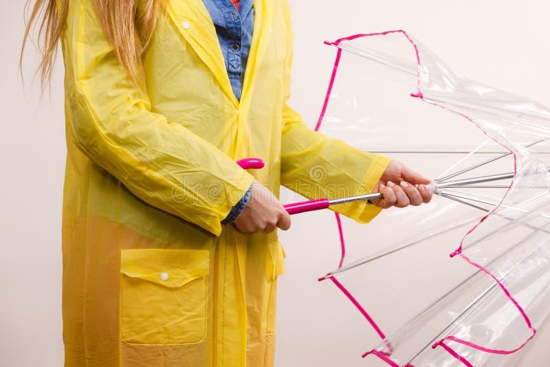 Donna che indossa l'ombrello impermeabile di apertura del cappotto fotografie stock libere da diritti