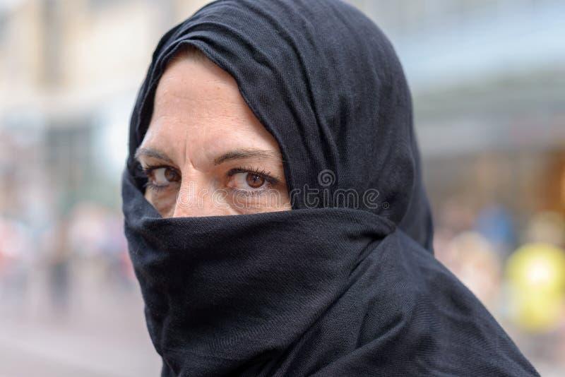 Donna che indossa un hijab con la bocca coperta immagini stock