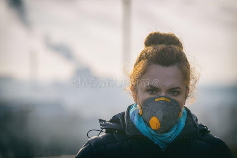 Donna che indossa una maschera antiinquinamento, dei virus reale e dello anti-smog di protezione fotografia stock