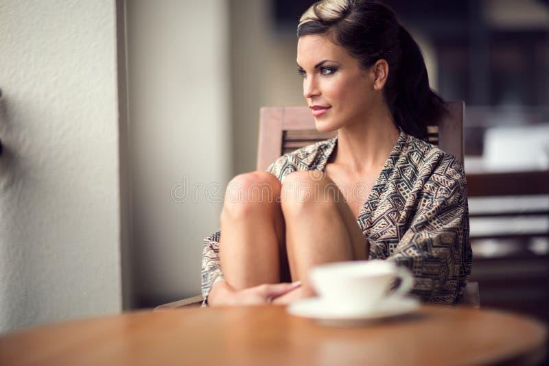 Donna che ingiunge in caffè di mattina immagine stock