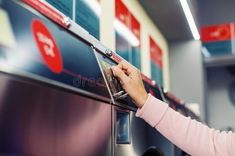 Donna che inserisce moneta in primo piano della lavatrice di self service immagini stock