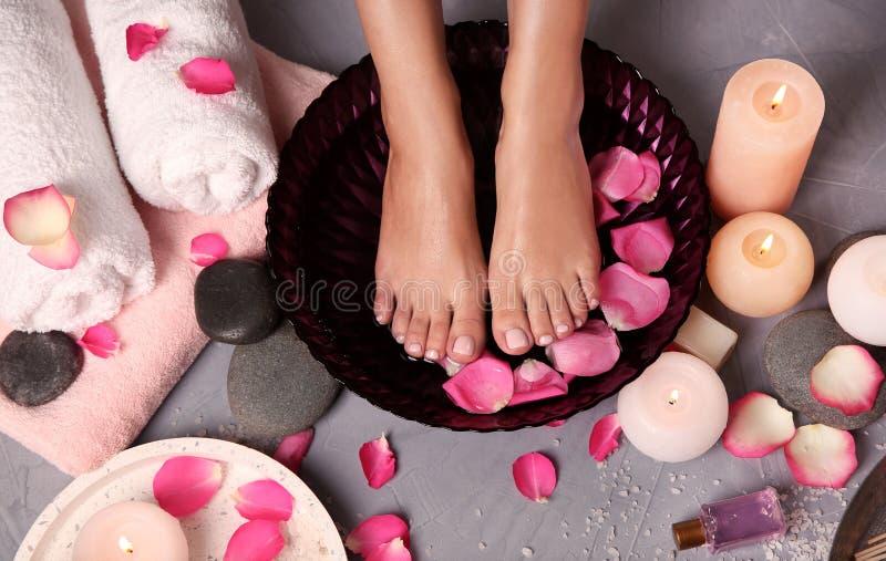 Donna che inzupparea i suoi piedi in ciotola nei petali di rosa e dell'acqua sul pavimento Stazione termale - 7 fotografie stock