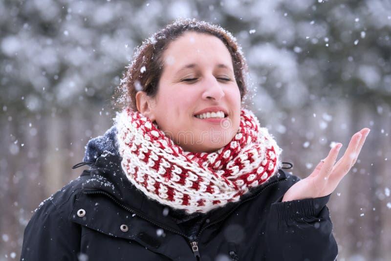 Donna che la chiude occhi e che sorride con la mano su come GE di cadute della neve fotografie stock