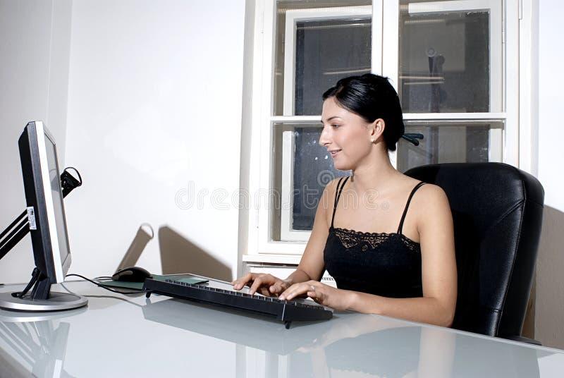 Donna che lavora ad uno scrittorio immagine stock