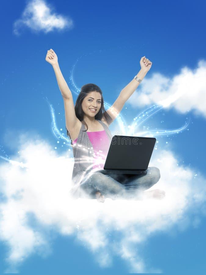 Donna che lavora al computer portatile in nuvola immagine stock libera da diritti