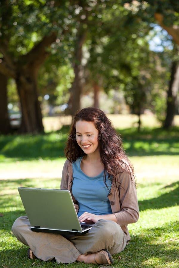 Donna che lavora al suo computer portatile immagine stock