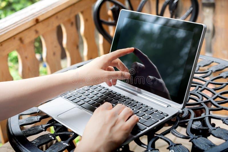 Donna che lavora all'aperto sul terrazzo, schermo commovente della compressa di affari immagini stock