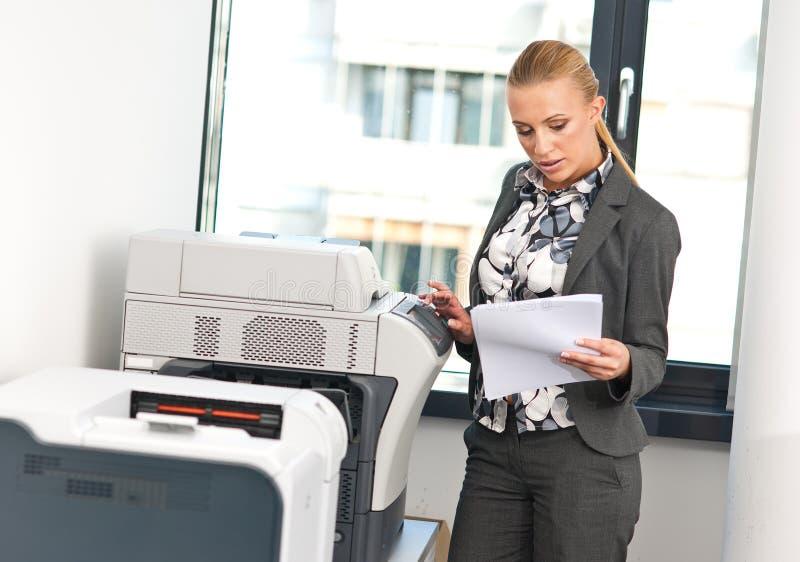 Donna che lavora alla macchina della copia fotografia stock