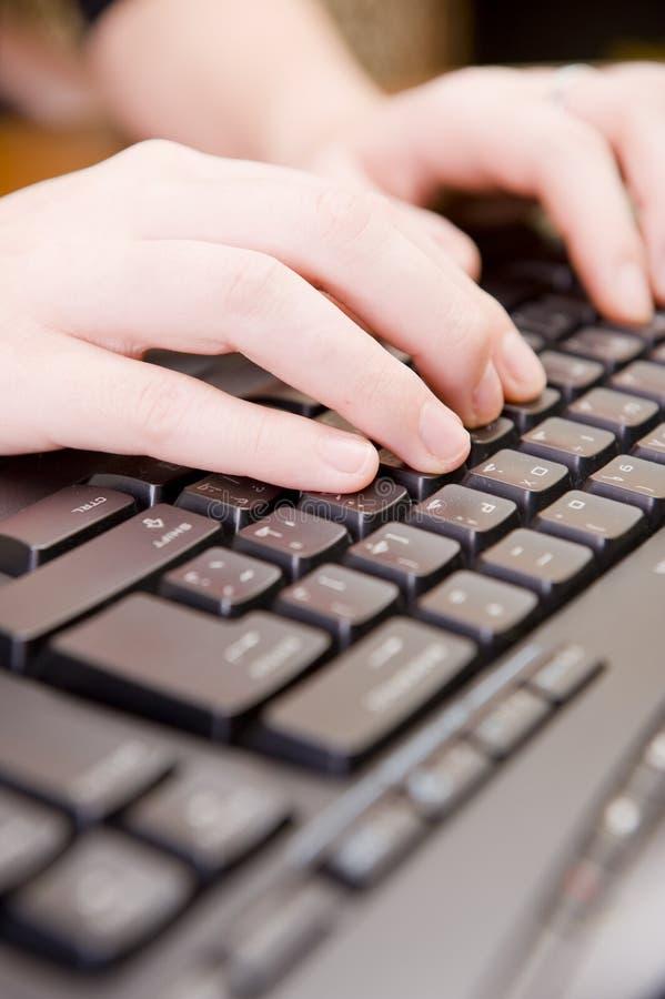 Donna che lavora alla tastiera ed al mouse del PC. immagini stock
