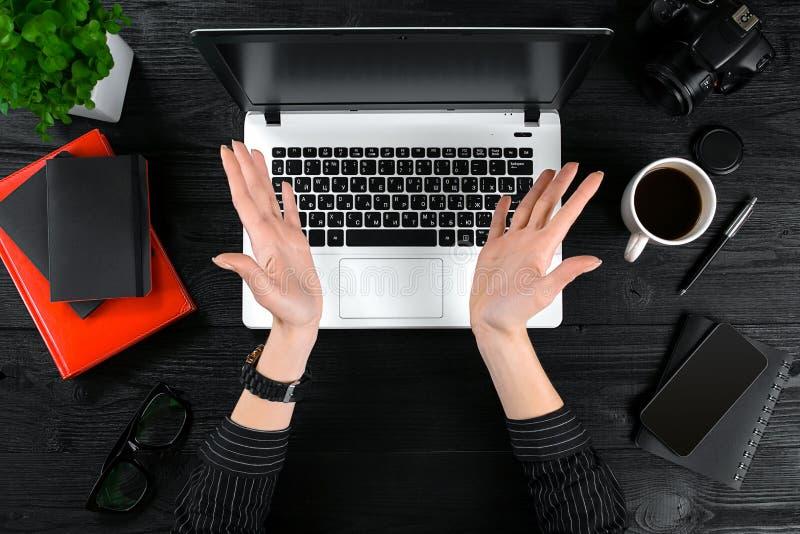 Donna che lavora alla tavola dell'ufficio Vista superiore delle mani umane, della tastiera del computer portatile, di una tazza d immagini stock