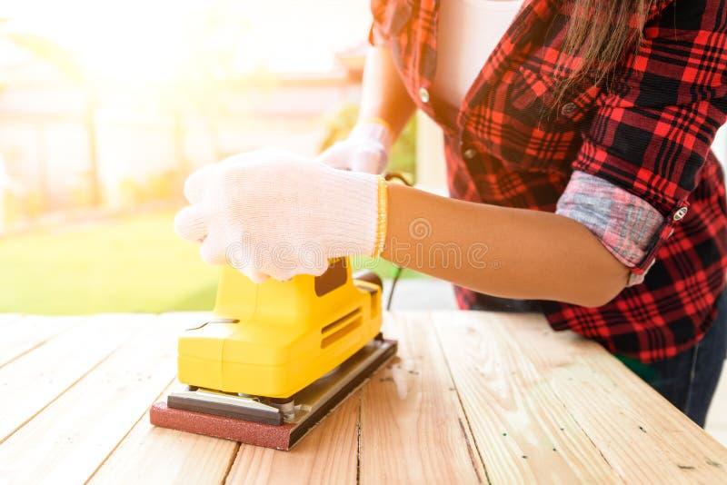 Donna che lavora con la macchina d'insabbiamento elettrica di legno fotografia stock