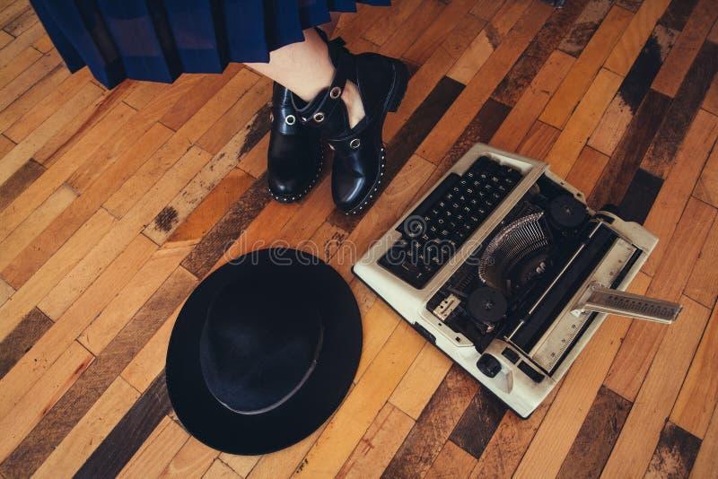 Donna che lavora con la macchina da scrivere sul pavimento di legno Vista superiore immagine stock
