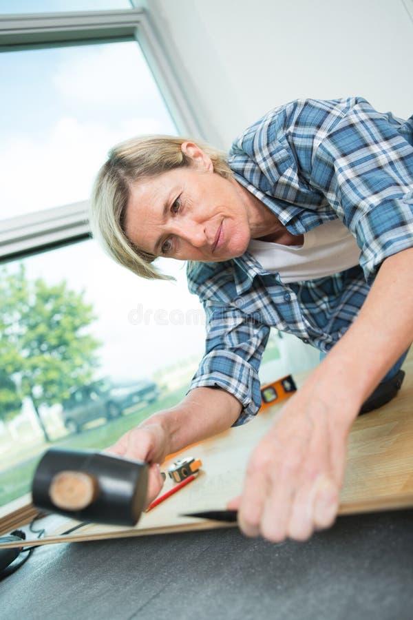 Donna che lavora con le tavole di pavimento immagine stock libera da diritti