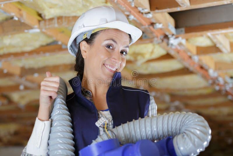 Donna che lavora con un tubo di ventilazione fotografia stock libera da diritti