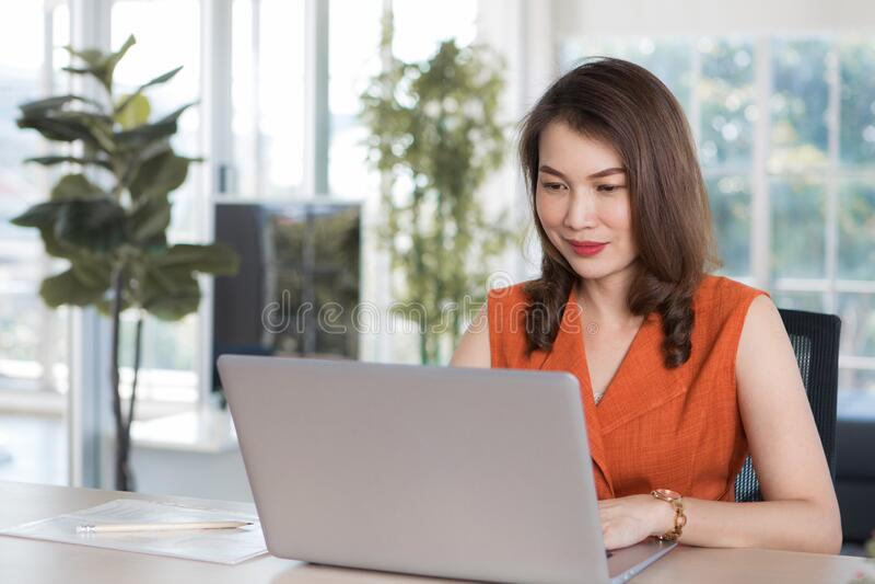 Donna che lavora da casa con il computer fotografia stock