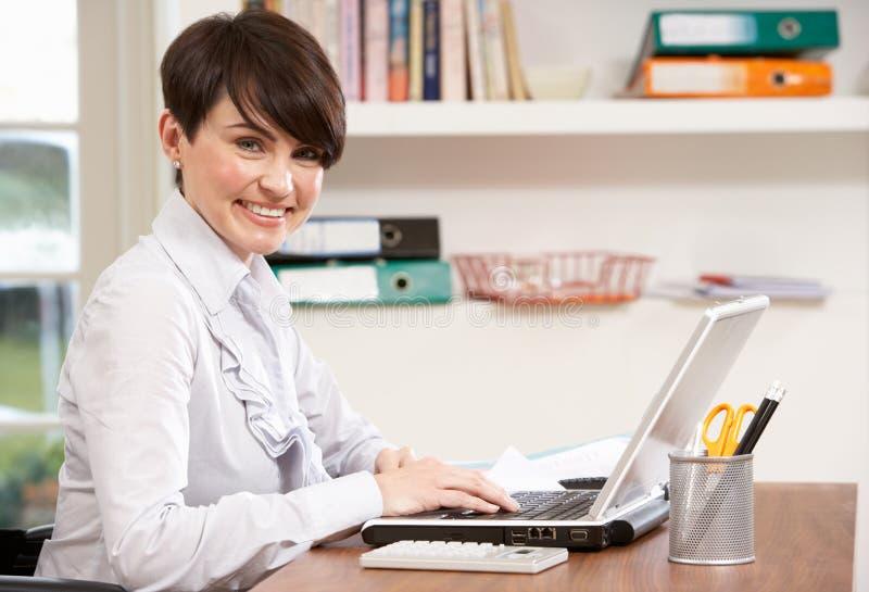 Donna che lavora dal computer portatile usando domestico fotografia stock