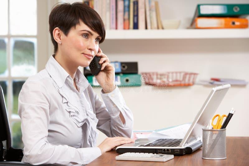 Donna che lavora dal computer portatile usando domestico sul telefono fotografie stock