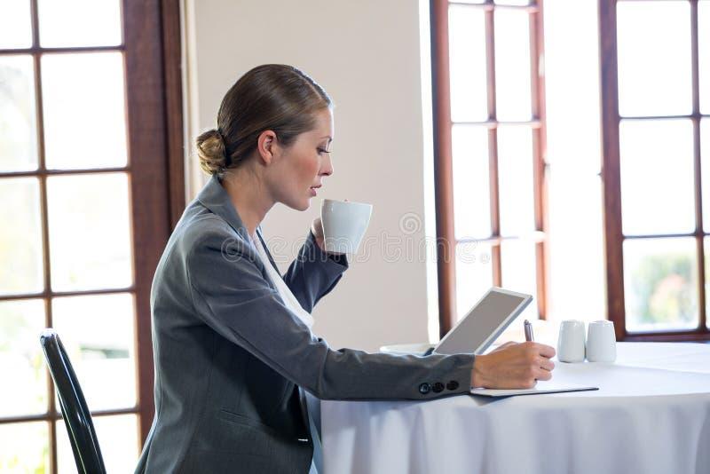 Donna che lavora e che beve un caffè fotografie stock libere da diritti