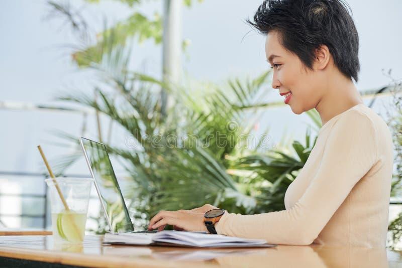 Donna che lavora online sul computer portatile fotografie stock libere da diritti