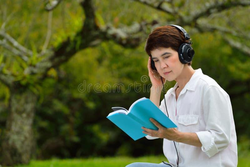 Donna che legge un libro e che gode della musica immagine stock libera da diritti