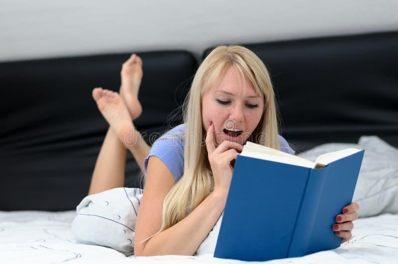 Donna che legge un libro mentre rilassandosi sul suo letto fotografia stock libera da diritti