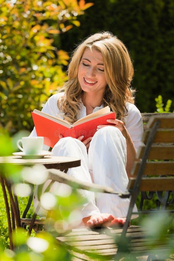 Donna che legge un libro nel giardino fotografia stock