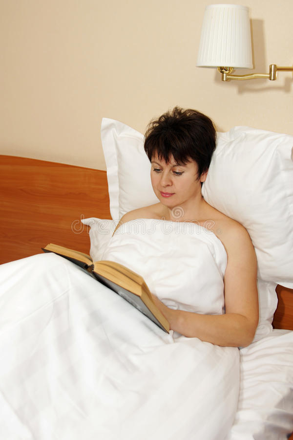 Donna che legge un libro nel letto fotografie stock libere da diritti