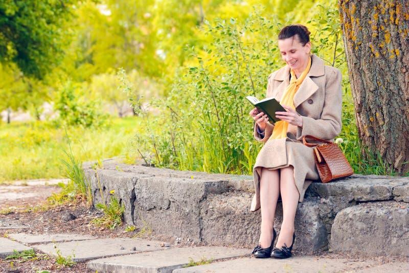 Donna che legge un libro nel parco in primavera immagini stock
