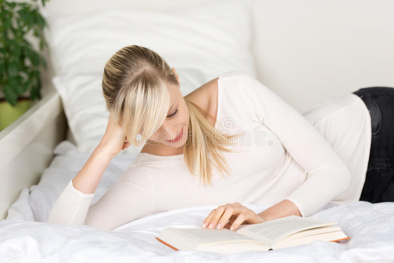 Donna che legge un libro sul suo letto fotografia stock