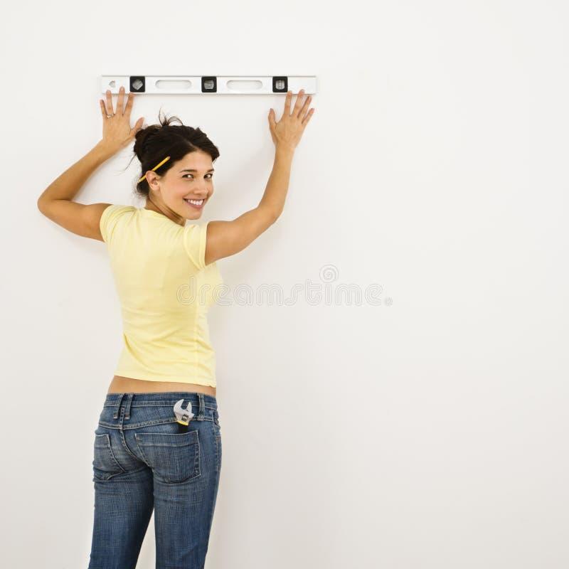 Donna che livella parete. fotografie stock