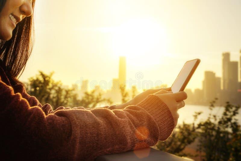 Donna che manda un sms sullo smartphone accanto al fiume nella stagione estiva immagini stock libere da diritti