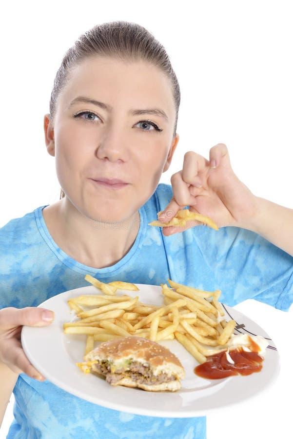 Donna che mangia alimenti a rapida preparazione immagine stock