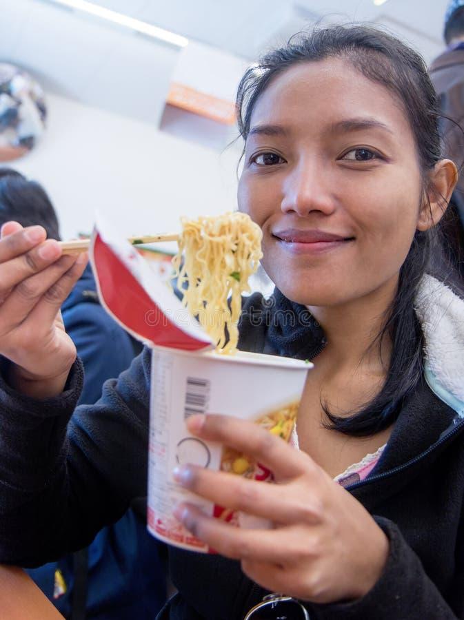 Donna che mangia alimento da una tazza di carta fotografie stock libere da diritti