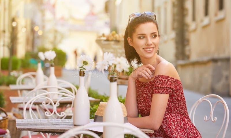 Donna che mangia caffè italiano al caffè sulla via in Toscana immagine stock